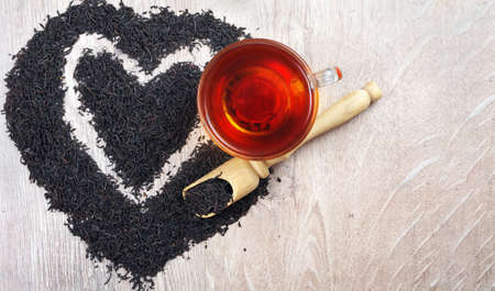 concept i like tea. a cup of black tea and dry black tea leaves on a wooden table. heart symbol made from black tea leaves. top view. copy space