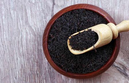 dry black tea leaves in a wooden bowl. black tea in a scoop. top view