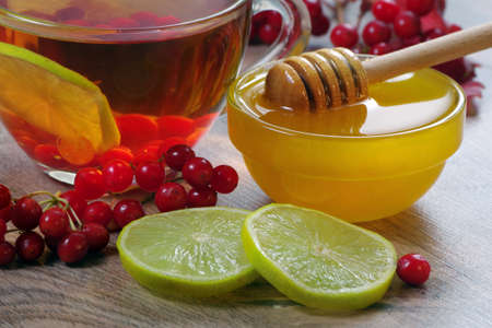 viburnum tea, honey and lime on a wooden table. medicine for colds and flu. alternative medicine