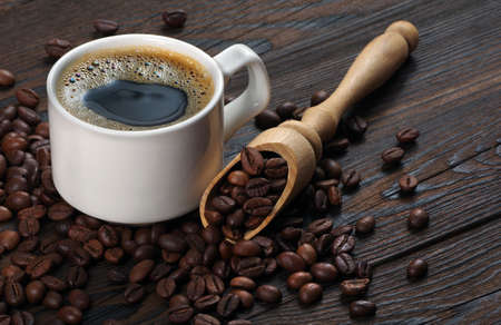 Coffee beans and cup of coffee on a wooden table. coffee in a white cup.