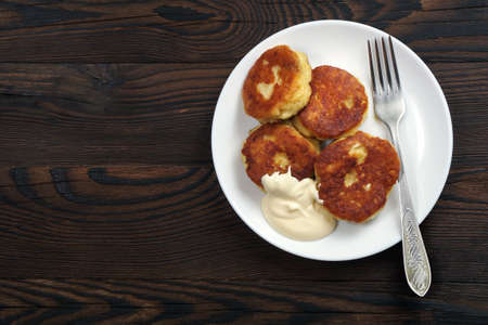 cheese pancakes and sour cream on a wooden table