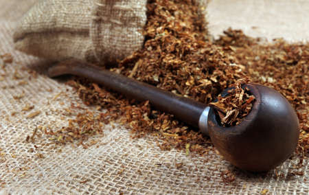 Smoking pipe and tobacco on a table. close up