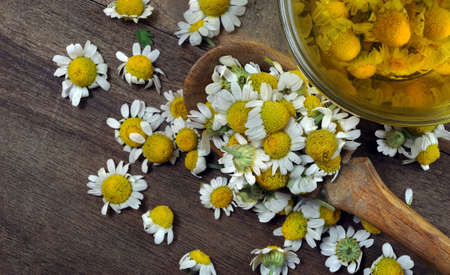 medicinal chamomile flowers in a wooden spoon and a cup of chamomile tea. summer herbal tea Stock fotó