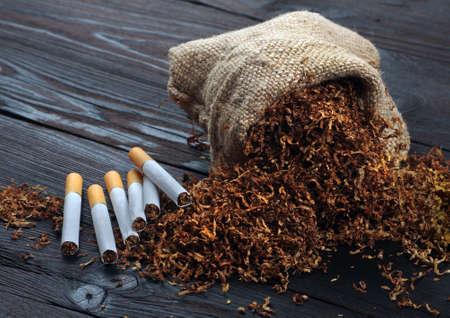 dry cut tobacco leaf and cigarettes on a wooden table. tobacco in a bag