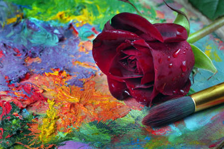 beautiful red rose and brush on artist's palette Фото со стока