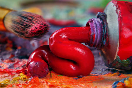 tube of red oil paint and a brush on the artist's palette Фото со стока - 168240271