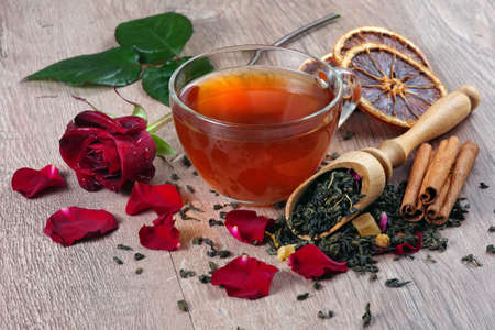 cup of green tea and red rose on a wooden table