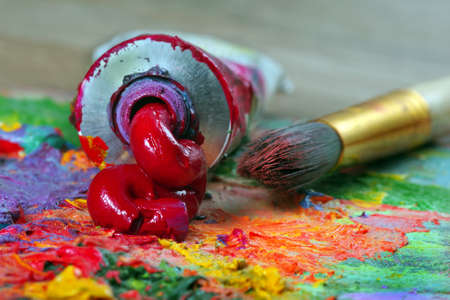 tube of red oil paint and a brush on the artist's palette