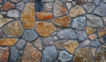 stone wall. wall of granite blocks. a masonry wall of multicolored stones or blocks
