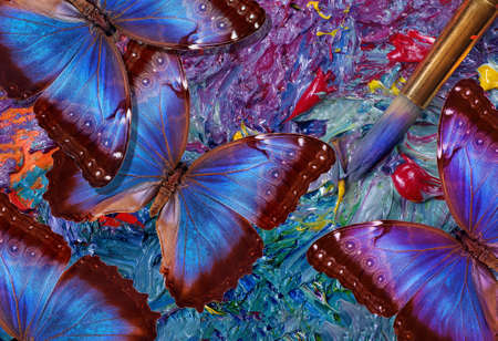 color concept. bright blue tropical morpho butterflies on an artist's palette. art paints and butterflies colorful background Фото со стока