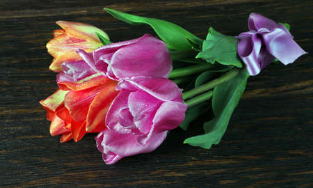 bright colorful bouquet of tulips on a wooden table. Фото со стока