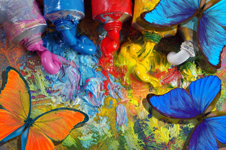 colors of rainbow. color concept. bright tropical morpho butterflies on an artist's palette with tubes. art paints and butterflies colorful background