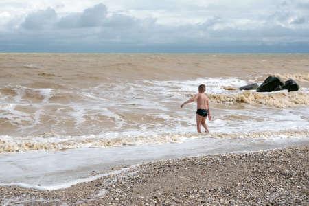 boy bathes in the sea. water games Фото со стока