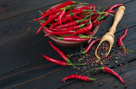 red hot chili peppers and a mixture of peppers in a wooden spoon on a wooden table. top view. traditional spices.