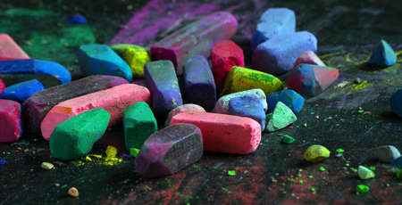 multicolored pastel crayons on black chalkboard close up