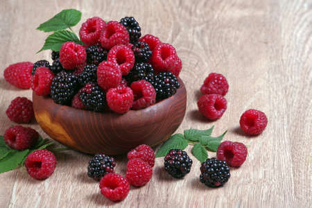 fresh ripe raspberries and blackberries in a wooden bowl. Standard-Bild