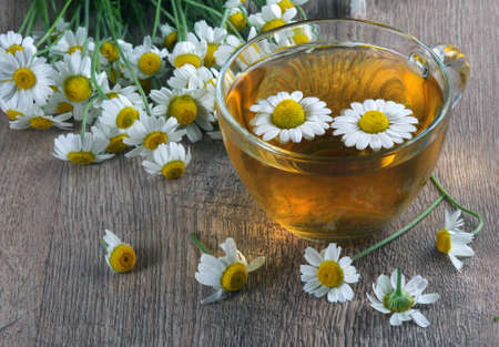 herbal chamomile tea in a glass cup on a wooden table. close up. medicinal herbs