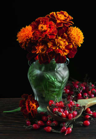 Tagetes. bouquet of marigolds in a glass vase and ripe red rose hips in a spoon on a black background Standard-Bild