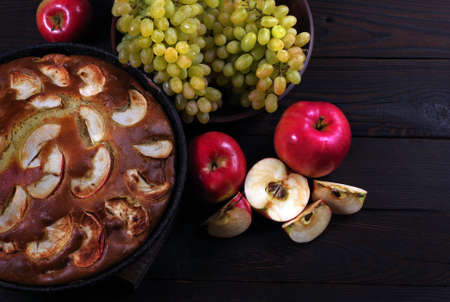 apple pie and fruits on a wooden table. top view