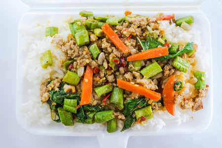 Rice topped with stir fried minced pork and basil in foam box. Thai food photo