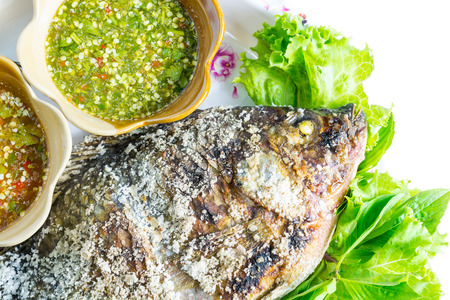 Close up tilapia grilled with vegetable isolate on white photo