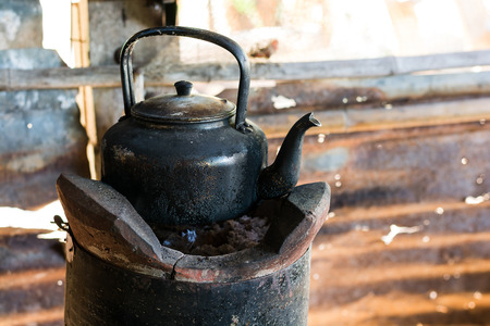 Old kettle for boiling water on stove In kitchen the countryside. photo