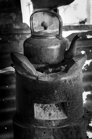 pioneers: old kettle for boiling water on stove In kitchen the countryside ,Black and white tone Stock Photo
