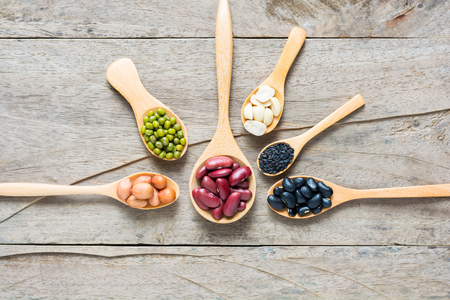 alubias: Grupo de los frijoles y lentejas en cuchara hecha de madera sobre fondo de madera.