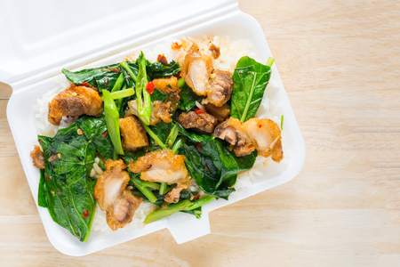 Crispy pork Stir-fried kale with steamed rice in Styrofoam food container on wood background. Foam Box Cause cancer and have the substance styrene (Styrene) hidden. Thai food. Stock Photo