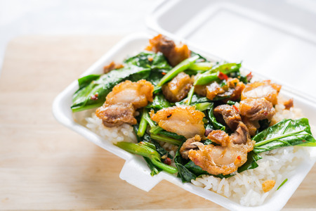 Crispy pork Stir-fried kale with steamed rice in Styrofoam food container. Foam Box Cause cancer and have the substance styrene (Styrene) hidden. Thai food.