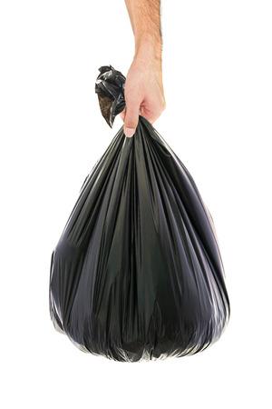 アジア男の手がゴミ袋を保持しています。
