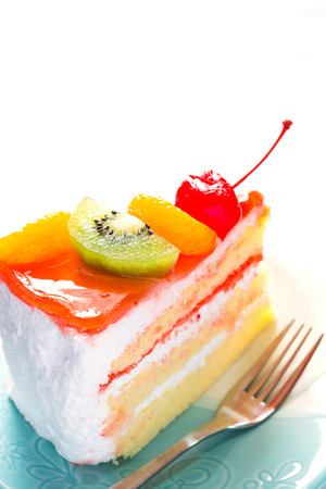 cake topping: Fruit cake delicious, cake topping with fruit decorated on dish on whitte background. Stock Photo