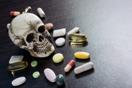 drug overdose: Skull and diferent Tablets pills capsule heap mix therapy drugs doctor flu antibiotic pharmacy medicine medical on dark background - Concept of a drug overdose caused fatal. Stock Photo