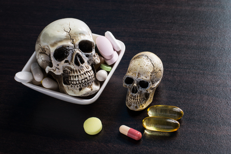 fatal: Skull and diferent Tablets pills capsule heap mix therapy drugs doctor flu antibiotic pharmacy medicine medical on dark background - Concept of a drug overdose caused fatal. Stock Photo