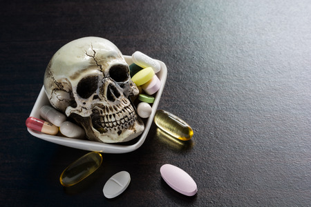 sobredosis: Skull and diferent Tablets pills capsule heap mix therapy drugs doctor flu antibiotic pharmacy medicine medical on dark background - Concept of a drug overdose caused fatal. Foto de archivo