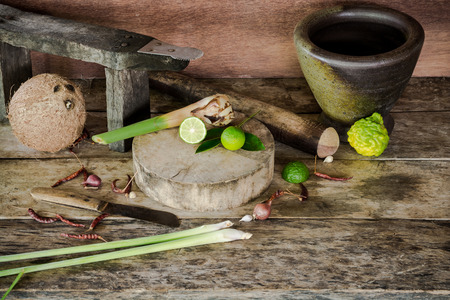 northeast: Herb and spicy ingredients of thai food on wooden background in the kitchen of the rural people in the northeast of Thailand; Wooden cutting boards, knives, dried chillies, onions, garlic, galangal, lemon grass, kaffir lime, mortar stone, pestle, coconut, Stock Photo