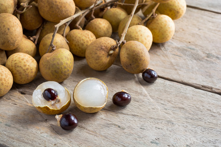 black seed: Longan Fresh (Dimocarpus longan.)A bunch of Longan and Peel show the white meat with black seed was placed on a wooden background. Stock Photo