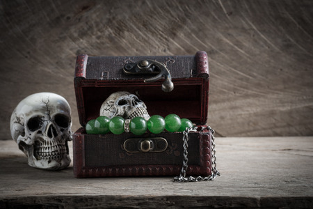 gruesome: Treasure chest old with Jewelry and human skull on wood background. Still life. Stock Photo