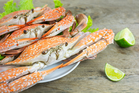 crab: Hot steamed blue swimming crab with vegetable on dish on wooden table background. Flower crab or blue crab or blue manna crab or sand crab from sea of south Thailand. Stock Photo