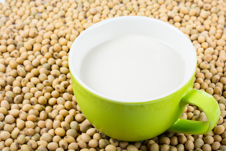 lecithin: Soy milk in a glass with soy beans on a white background. Stock Photo