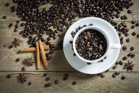 estrella de la vida: Granos de café en la taza de café con leche y canela en rama y especias anís de estrella en el fondo de madera. Bodegón