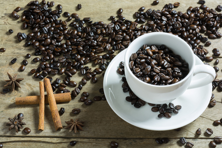 star of life: Coffee beans in white coffee cup and cinnamon stick and star anise spice in wooden background. Still Life
