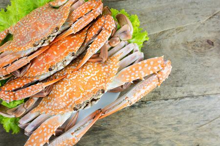 cangrejo: Caliente al vapor cangrejo azul de nataci�n con verduras en el plato en el fondo mesa de madera. Flor cangrejo o el cangrejo azul o cangrejo azul man� o cangrejo de arena de mar del sur de Tailandia. Foto de archivo