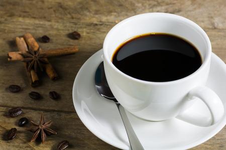 estrella de la vida: Los granos de café y taza de café blanca con canela y especias anís de estrella en el fondo de madera. Bodegón Foto de archivo