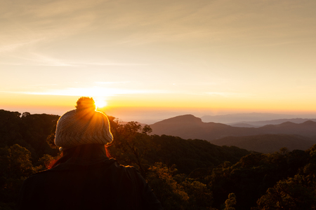 The girl wears a winter coat and beautiful winter sunrise landscape viewpoint at km.41 of Doi Inthanon Chiang Mai Thailand. Standard-Bild