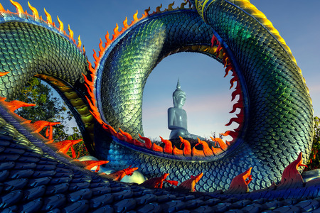 Thai Naga Statue and big Buddha statue in Phu Manorom Temple at Mukdahan, Thailand Built on mountain along the Mekong River, overlooking the banks of Laos. Standard-Bild