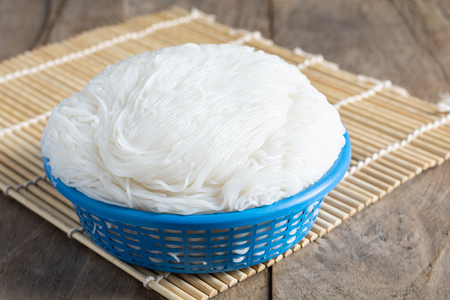 Rice vermicelli white In a blue basket on wood table Is a savory food that Thai people prefer popular to eat.