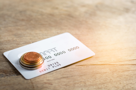 White credit cards and coins on wood background. Financial concept