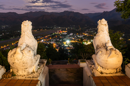 Mae Hong Son city view from wat phra that doi kong mu temple in twilight sunset with white lion statue, thailand.