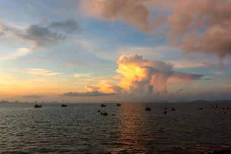 Fishing boat floats in sea with sunrise shining and with cloud. View from Koh Larn, Chon Buri THAILAND.